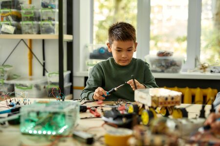 Young professional. Asian boy using soldering iron to join chips and wires while making his own vehicle at a stem robotics class. Inventions and creativity for children.