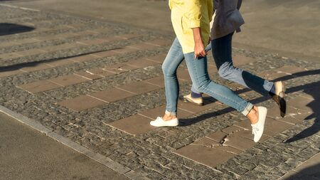 Cropped photo of a couple in casual clothes running across the street Stock Photo