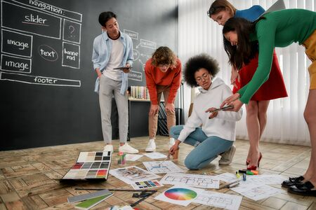 Team job. Group of professional team of interior designers discussing sketches, choosing colors from palettes lying on the floor in the modern office. Creative agency