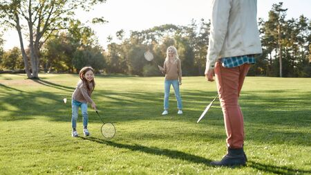 Developing through fun and creativity. Parents play with daughter in badminton in the park on a sunny day