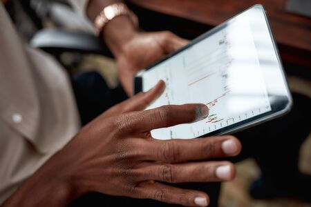Nurture the future. Close up shot of hands holding tablet pc. Trader is using touch screen tablet for analyzing stock market chart, while working in the office