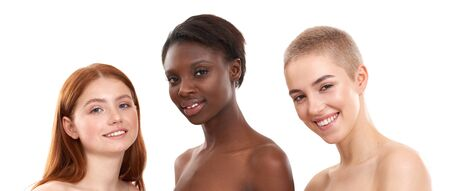 We are all beautiful. Three positive multicultural young women looking at camera and smiling while posing in studio over white background. Two caucasian and african half naked women