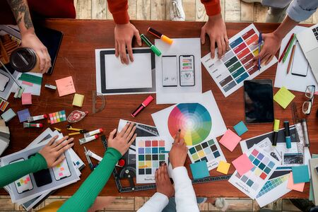 Mobile app design. Top view of designers discussing sketches, choosing colors from palettes lying on the desk while having a meeting in the modern office Standard-Bild