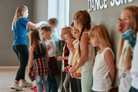 Dance class. Group of cute and positive children with young female teacher standing at the dance studio. Choreography concept