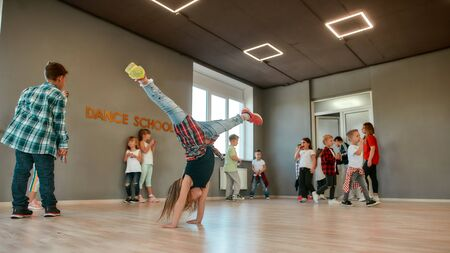 Full length portrait of a little girl standing on her hands while having a choreography class in the dance studio. Children dancing. Breakdance style. Kids and sport