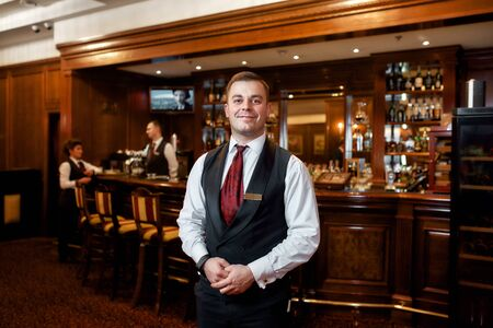 Have a nice evening. Portrait of smiling waiter welcoming guests in hotel restaurant