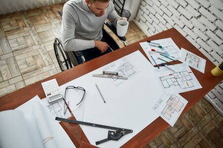 Top view of young male architect in a wheelchair looking at blueprint and drinking coffee while sitting at his workplace in the modern bright office. Construction concept