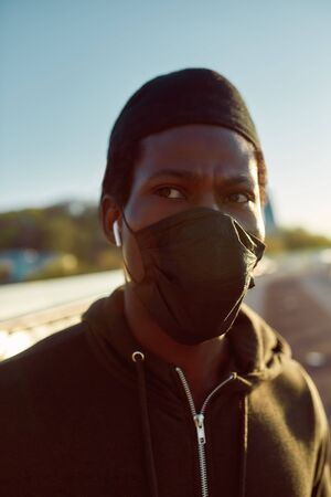Run. Close up portrait of african runner wearing medical protective mask and looking away. Jogging, running. Sport during quarantine. Covid-19