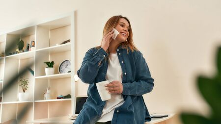 Happy to hear you. Young beautiful happy woman in casual clothes talking by phone with friend or client, drinking coffee or tea while working from home