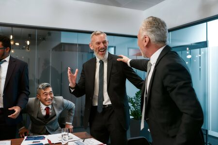 Happy to work with you. Two cheerful business colleagues in formal wear laughing while having a meeting in the modern office