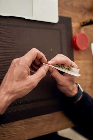 Close up of hands of man making, rolling a marijuana cigarette or joint, sitting at home, in the kitchen. Marijuana grinder on the table. Cannabis legalization concept. Vertical shot Stock Photo