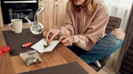 Cropped shot of young caucasian woman putting weed in a tube while sitting in the kitchen. Bong, buds in a plastic bag, marijuana grinder and lighter on the table. Cannabis legalization concept 免版税图像