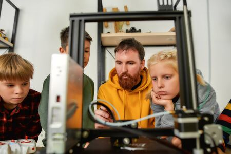 Innovation. Education. Curious kids are learning about working principle of 3d printer from their male teacher at robotics school lesson