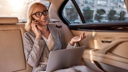 Happy to hear you. Happy and beautiful business woman in full suit working on laptop and talking on the phone while sitting in the car
