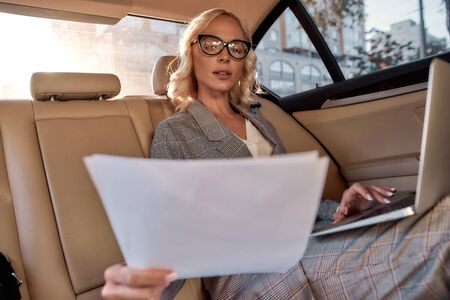 Reading contract. Beautiful and successful business woman in full suit analyzing documents and working on laptop while sitting in the car