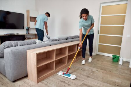 Top quality janitorial team. Two professional cleaners working together in the living room. Young afro american woman cleaning floor with mop while her male coworker cleaning sofa with handheld vacuum