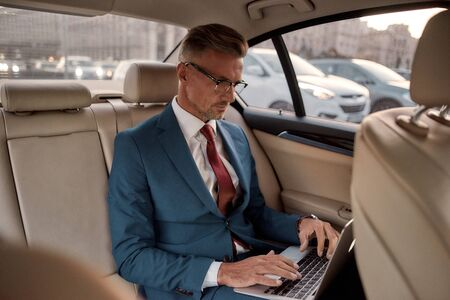 Setting goals. Serious mature businessman in full suit working on his laptop while sitting in the car Banque d'images