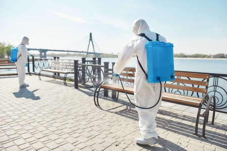 Infection Control. Sanitization, cleaning and disinfection of the city due to the emergence of the Covid19 virus. Specialized team in protective suits and masks at work near the riverside 写真素材