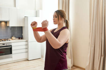 Live stronger. Young curvy woman in sportswear exercising using resistance band at home