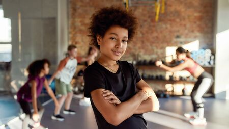 Get stronger here. Portrait of a boy smiling at camera before warming up, exercising together with other kids and trainer in gym. Sport, healthy lifestyle, active childhood concept