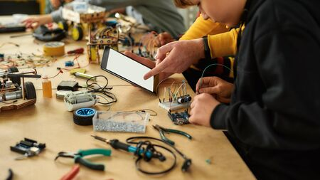 Cropped shot of young technicians working with a wiring kit at a stem robotics class. Male teacher helping them, giving advice, using tablet pc. Tinkering, educational activities concept. Web Banner