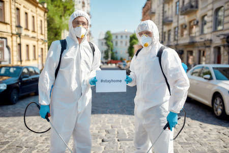 Stay Alert. Cleaning and disinfection of the streets in the city due to the emergence of Covid19 virus. Specialized team in protective suits and masks holding a card with the inscription Stay Home