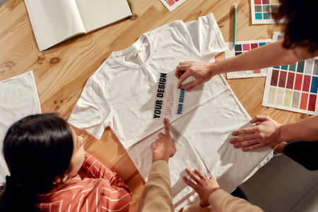 Writing that sells. Creative people trying on stickers with text, while discussing logo and design of T-shirt. Young man and women working together at custom T-shirt, clothing printing company