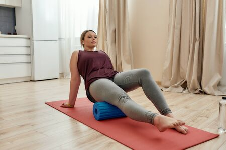 Gym at home. Full length shot of young curvy woman in sportswear exercising using foam roller on a yoga mat at home