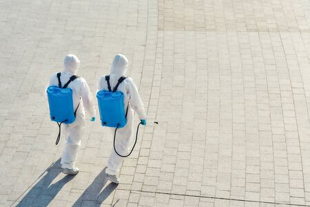 We care for you. Sanitization, cleaning and disinfection of the city due to the emergence of the Covid19 virus. Specialized team in protective suits and masks walking outdoors Banque d'images