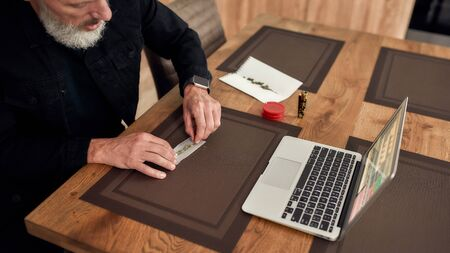 Reduce anxiety. Middle-aged man, artist making a marijuana cigarette or joint, sitting at home, in the kitchen and writing song using laptop. Marijuana grinder, lighter and weed on the table