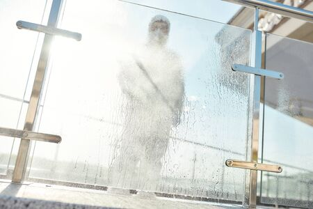 Better than clean. Sanitization, cleaning, disinfection of the city due to the emergence of the Covid19 virus. Man in protective suit and mask at work, sanitising glass surface. Blurred image