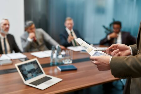 Blurred photo of a businessman holding a financial report and explaining something to multicultural business team while having a meeting