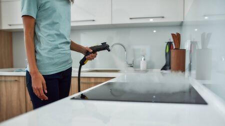 Cropped view of a woman in uniform cleaning electric stove with steam cleaner while working in the modern kitchen. Cleaning services concept