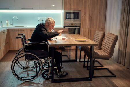 止痛药。坐在轮椅上的残疾老人在厨房的玻璃水管或烟枪中点燃大麻。桌子上有大麻工具。德赢体育毒品合法化与轻毒品依赖的概念