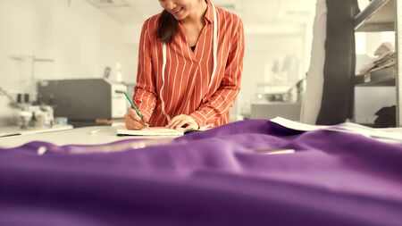 Cropped shot of young female clothing designer leaning against the desk with fabric and sewing supplies on it, while planning new collection and writing notes. Selective focus Stock fotó