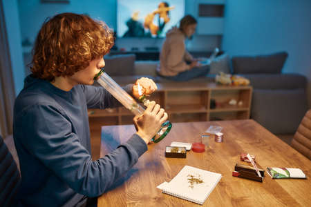 Device for smoking marijuana. Young guy lighting bong with cannabiswhile sitting in the kitchen at home . Woman using laptop on the background Stock fotó