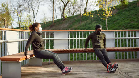 Keeping distance. African couple in protective masks working out in park outdoors. Doing push-ups exercises on bench, training triceps. Social distancing 免版税图像