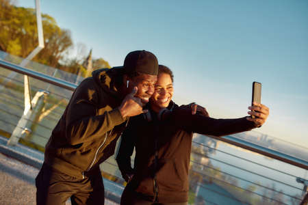 Taking selfie after run. Young cheerful african couple in sportswear taking selfir and smiling while standing on the bridge in the morning