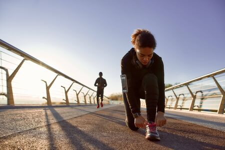 Getting ready for jogging. African sporty woman in black sportswear tying shoelaces before run on the bridge in the early morning. Running at sunrise. Sport. Healthy and active lifestyle
