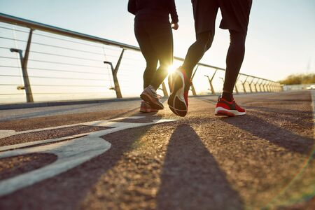 Bak view of a couple in sportswear running together on the bridge in the morning. Cropped shot. People are running outdoors. Sport. Active morning. Healthy lifestyle