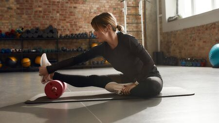 Sportive woman sitting on a yoga mat, using foam roller while having workout at industrial gym. Healthy lifestyle concept. Horizontal shot. Side view 版權商用圖片