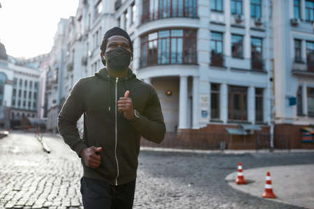Keep the Distance. Young african athletic man in black sportswear and medical protective mask running through the city street in the morning. Close up 免版税图像