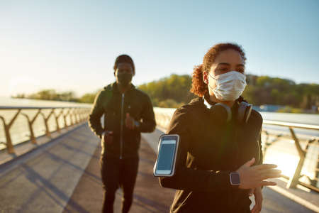 Young african man and woman in medical masks running on the bridge during a pandemic. Sport and coronavirus