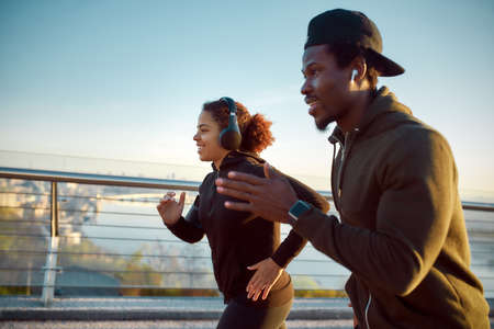 Morning run. Side view of happy sporty African couple in headphones jogging together on the bridge in the early morning. Happy African man and woman running and listening music