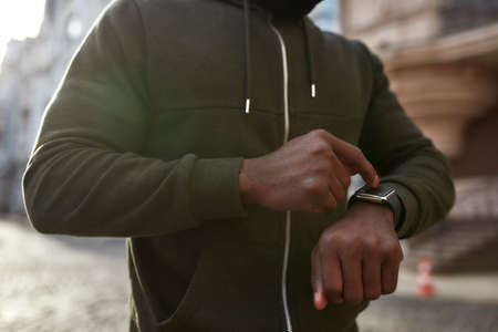 Using fitness app. Cropped photo of african male runner in black sportswear touching his smartwatch while running outdoors in the morning