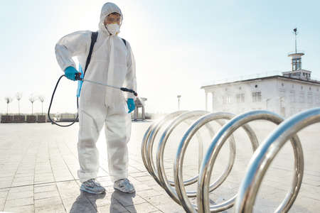 The clean you expect. Sanitization, cleaning, disinfection of the streets and alleys in the city center due to the emergence of the Covid19 virus. Man in protective suit and mask at work Banque d'images