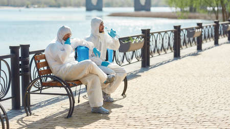 Hard workers. Sanitization, cleaning and disinfection of the city due to the emergence of the Covid19 virus. Specialized team in protective suits and masks takes a break near the riverside