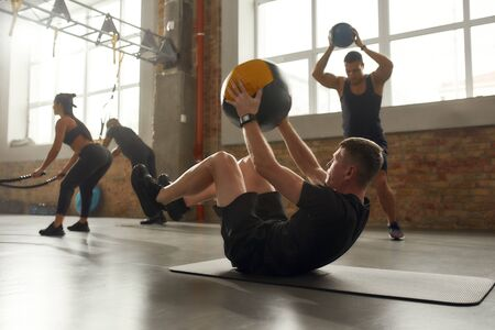 Sportive man using exercise ball while having workout at industrial gym. Group training, teamwork concept. Horizontal shot
