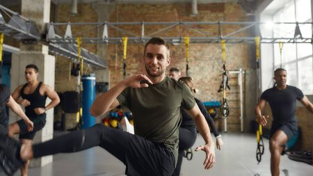 In Pursuit of Good Health. Athletic caucasian man in sportswear smiling at camera while working out in industrial gym. Group training concept