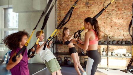 Dedication. Portrait of female trainer controlling, looking after kids while they are working out with fitness straps in gym. Sport, healthy lifestyle, physical education concept